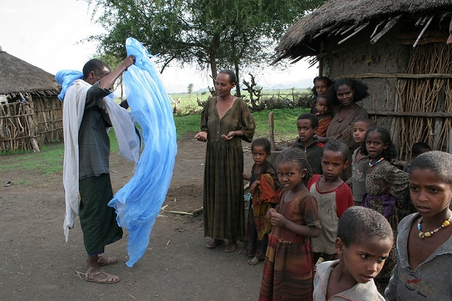 A man educates a community in Ethiopia on the uses of insecticide treated nets (ITNs).