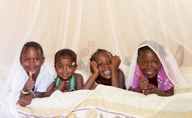 Young girls in Senegal lie in bed under a mosquito net.