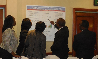 Attendees review a poster at the Zambia close out event.